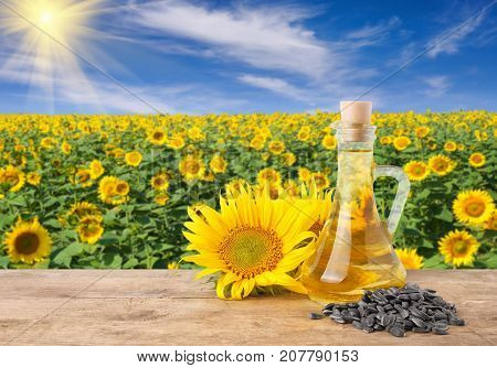sunflower oil in glass bottle, pile of sunflower seeds, fresh sunflowers on wooden table with natural background. Blooming sunflower field with blue sky and sun. Agriculture and harvest concept