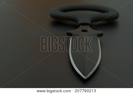 Black Knife On Black Background. Copyspace.