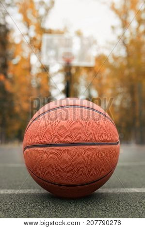 basketball ball on the outdoors court with basketball hoop on the background. Sport equipment