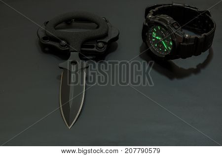 Black Knife And Black Watch On A Black Background.