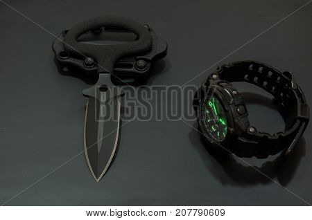 Black Knife And Black Watch With Highlighted Arrows.