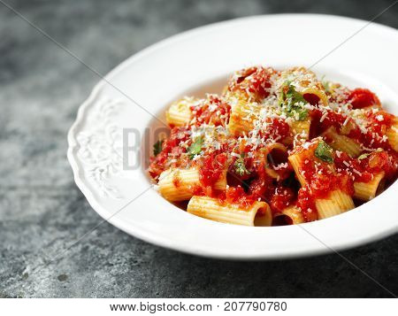 close up of rustic italian rigatoni pasta in tomato sauce