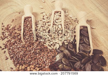 Flaxseed, Pumpkin, Raisins, Lentils And Sunflower Seeds In Wooden Spoons.