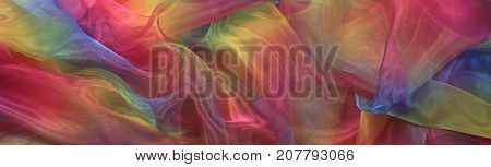 Beautiful Cascading Rainbow Chiffon Banner Background - Wide shimmering rainbow colored chiffon material cascading in gentle folds