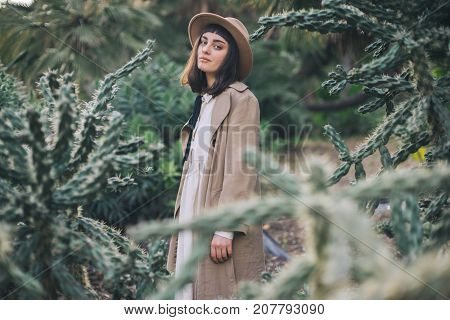 Dreamy brunette girl walks in cacti park wearing old fashioned white dress and brown hat poster