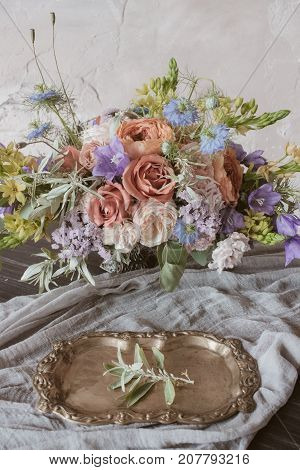 Analog film styled photo of beautiful wedding composition of roses in pastel shades with vintage salver