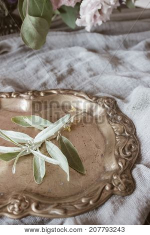 Analog film styled photo of beautiful wedding composition of vintage salver with green leaf and grey handcrafted gauze