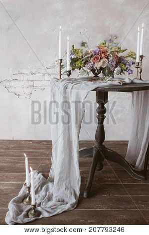 Analog film styled photo of beautiful wedding bouquet of roses in pastel shades with candles in vintage candlesticks