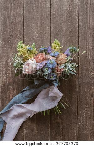 Analog film styled photo of beautiful wedding bouquet of roses in pastel shades with ligt pink and grey tapes on wooden dark floor