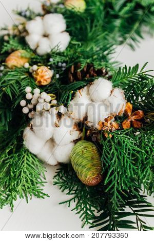 Christmas handmade wreath with coniferous branches cotton flowers silver brunia and leucadendron close up view