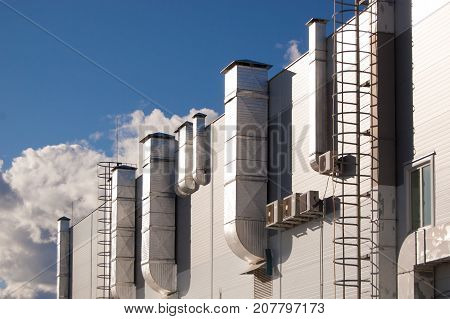industrial building with ventilation pipes and air conditioners against the blue sky