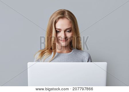 Concentrated Female Model Reads Attentively News Online, Being Focused In Screen Of Laptop Computer,