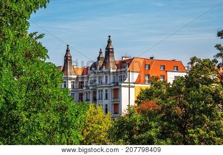 Part view of beautiful historic building in Wroclaw through green trees and branches over blue sky