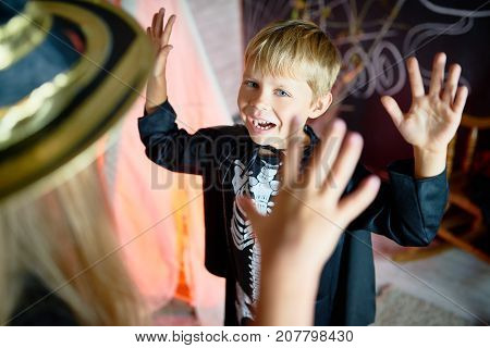 Portrait of little children having fun on Halloween, focus on cute little boy roaring like monster