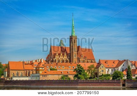 View of Church of Holy Cross and St. Bartholomew on Tumski Island. Cityscape of  Wroclaw, Poland, Odra River, blue sky.