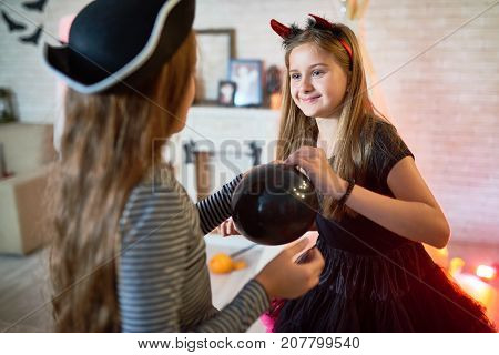 Portrait of two pretty gills wearing costumes decorating room for Halloween smiling happily and holding balloons