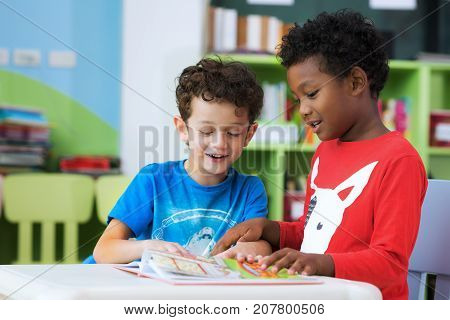 Student in international preschool reading a magazine book together in school library education kid and study concept