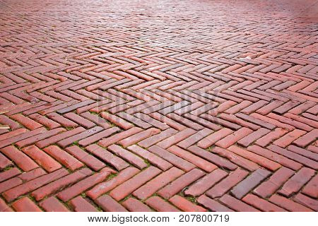 Abstract Grunge Red Stone Perspective Background. Decorative pavement with the herringbone pattern. The cobblestones on the streets of Amsterdam Netherlands