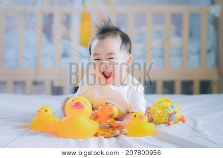 Asian New born baby sit and play an animal toy on the bed boy kid baby play and relax concept