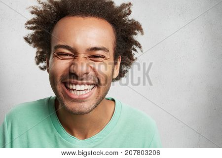 People, Happiness And Pleasant Emotions Concept. Cheerful Overjoyed Young Man With Afro Hairstyle An