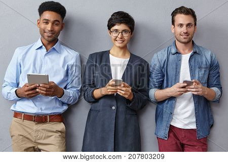 Friendy Mixed Race Team Of Business Workers Work With Modern Technologies, Wear Fashionable Clothes,