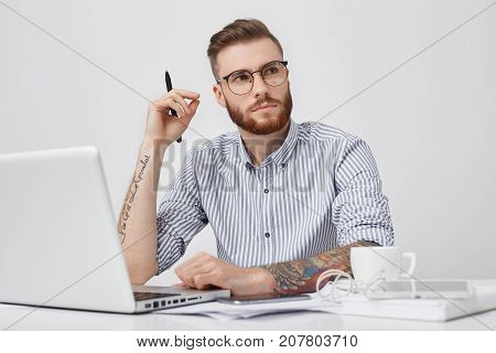 Pensive Clever Male Student With Trendy Haido Looks Thoughtfully Aside As Tries To Gather Thoughts,