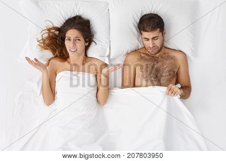 Indoor Shot Of Upset Female In Bed Shrugging Shoulders In Confusion, Worrying About Her Husband Who