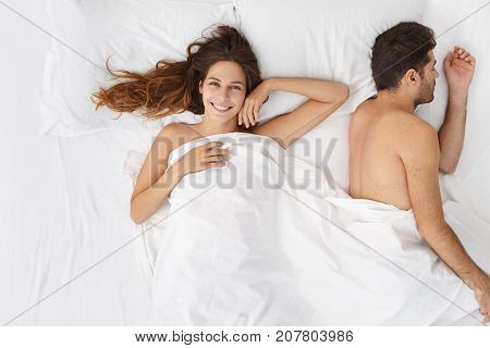 Portrait Of Overjoyed Pretty Woman Lying Under White Blanker Resting In Bed Together With Her Boyfri