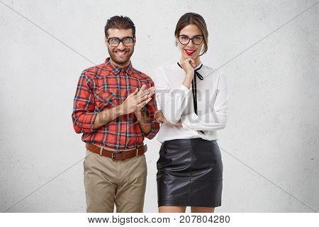 Indoor Shot Of Confident Cheerful Bearded Male Geek Keeps Palms Together, Being Delightful With Some