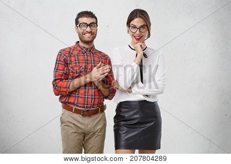 Portrait Of Smiling Weird Man Keeps Hands Together As Has Nice Idea Stands Near His Best Female Frie