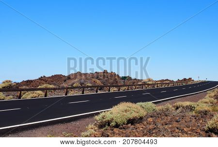 empty two lane black road stretching to the horizon in desert scrub with blue sky and white lane markings