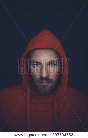 Portrait of a handsome man in mid thirties shot in studio wearing a red hooded sweatshirt on a dark blue wall.