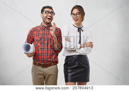 Positive Glad Male With Comic Expression Keeps Fingers Crossed, Looks Joyfully At Beautiful Female W