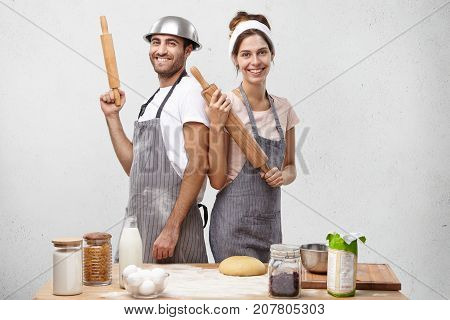 Indoor Shot Of Smiling Cooks Stand Back To Each Other, Hold Rolling Pins In Hands, Prepare Dough For