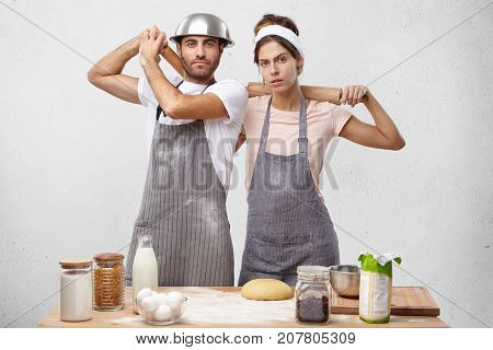 Confident Woman And Her Husband, Have Serious Expressions, Hold Rolling Pins Behind Backs, Ready To