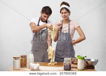Puzzled Couple Look At Bad Made Dough, Have Unsuccessful Day, Did By Wrong Recipe, Failed To Prepare