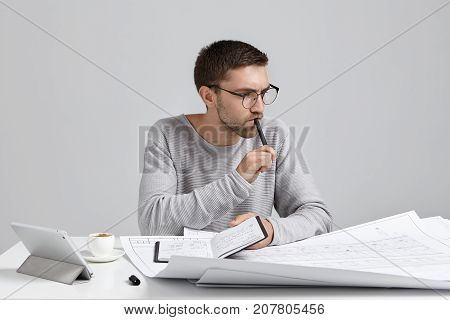 Serious Pensive Male Engineer Keeps Pen And Notebook In Hands, Plans Meeting, Look At Drawings And S