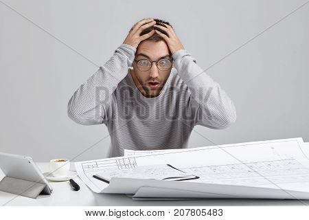 Crazy Overworked Architect Has Deadline, Keeps Hands On Head, Being In Panic, Stares At Blueprints,