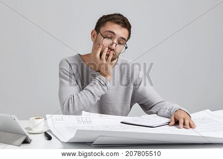Portrait Of Attractive Man Wears Round Glasses, Looks Puzzled Into Blueprints, Has No Idea How To Dr