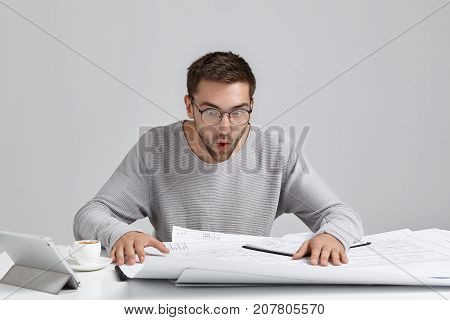 Portrait Of Male Engineer Stares At Drawings, Looks In Surprised Expression, Tries To Understand Wha