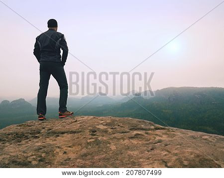 Nature Hiker On Sharp Cliff Roc Watching Over Misty  Valley To Blurred Horizon. Terrible Rainy Weath