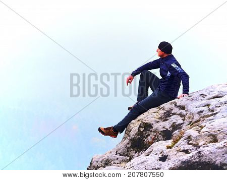 Adult Tourist In Black Trousers, Jacket And Dark Cap Sit On Cliff's Edge And Looking Into Mist