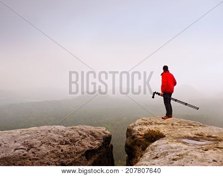 Photographer Think About Picture On Peak  In The Misty Mountains. Valley Hidden In Heavy Mist