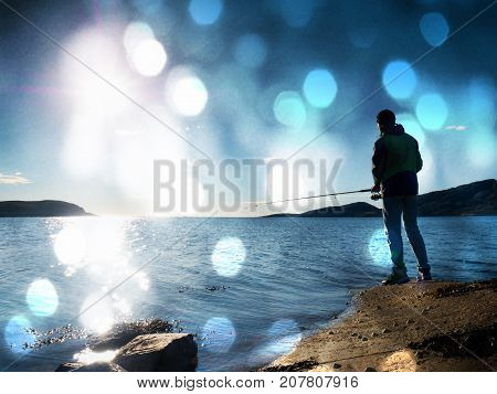The Active Man Is Fishing On Sea From The Rocky Coast. Fisherman Check Pushing Bait On The Fishing L