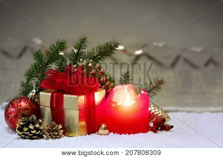 Christmas decoration with red bauble and candle for Advent .Red candle with christmas ball in atmospheric light.