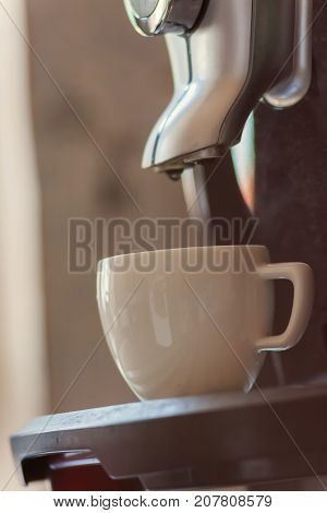 White Cup Standing On The Grating Of Coffee Machine With Coffee Pouring In The Cup In The Restaurant