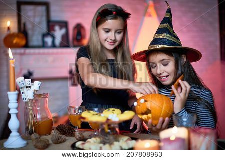 Pretty little sisters wearing fancy costumes decorating living room for Halloween party and anticipating arrival of their guests