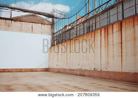 Empty backyard of old prison with rusty streaks on walls grid and barbed wire fence under blue sky with clouds.