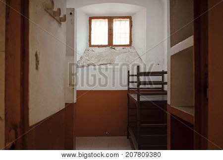 Sunlight through little window with grate and metallic double level bed and shabby old walls in cell room for prisoners.