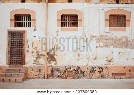 Old shabby wall with door little windows and grates looking at courtyard of prison